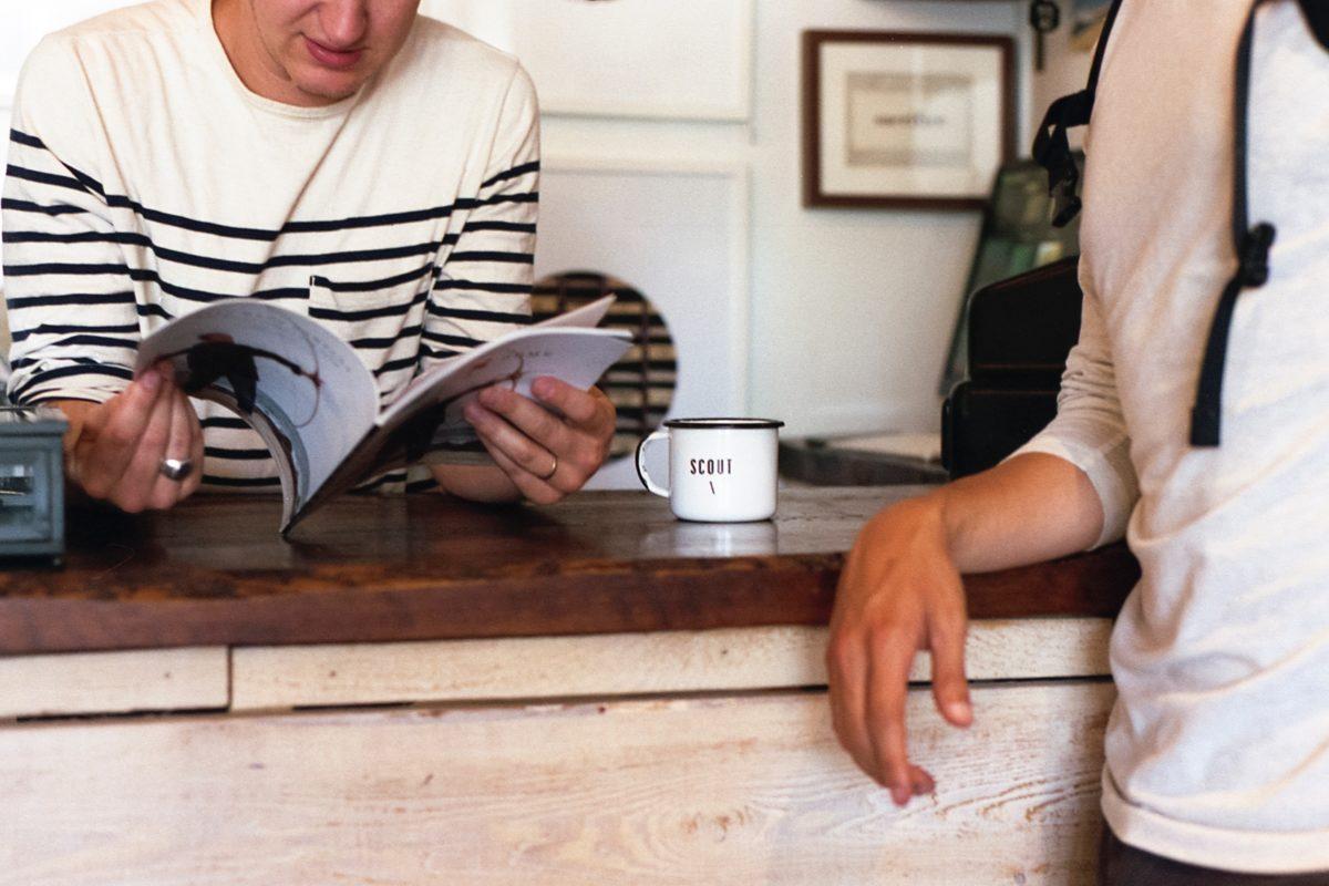 Närbild på två personer vid en bänk. Den ena läser i en katalog.