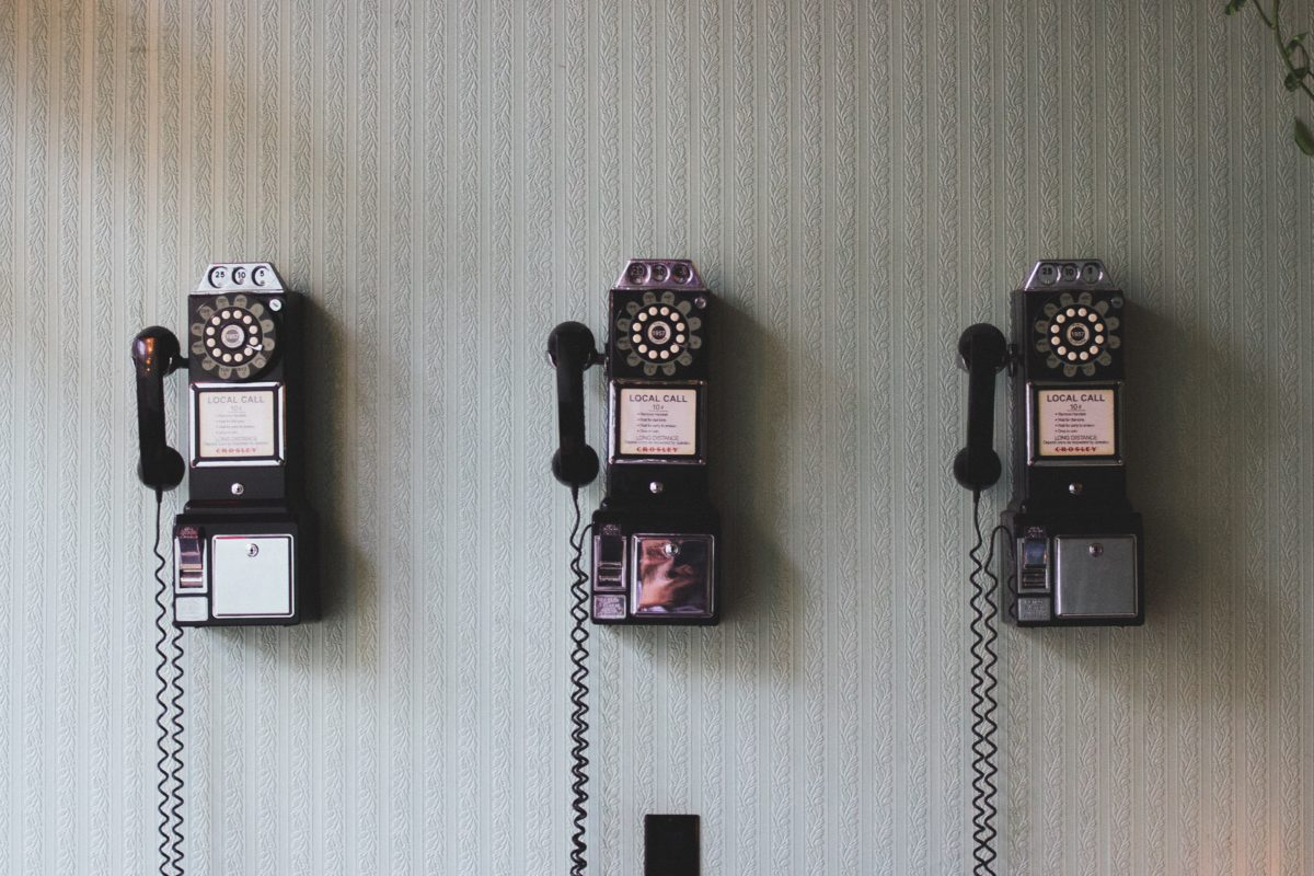 three vintage phones on a wall