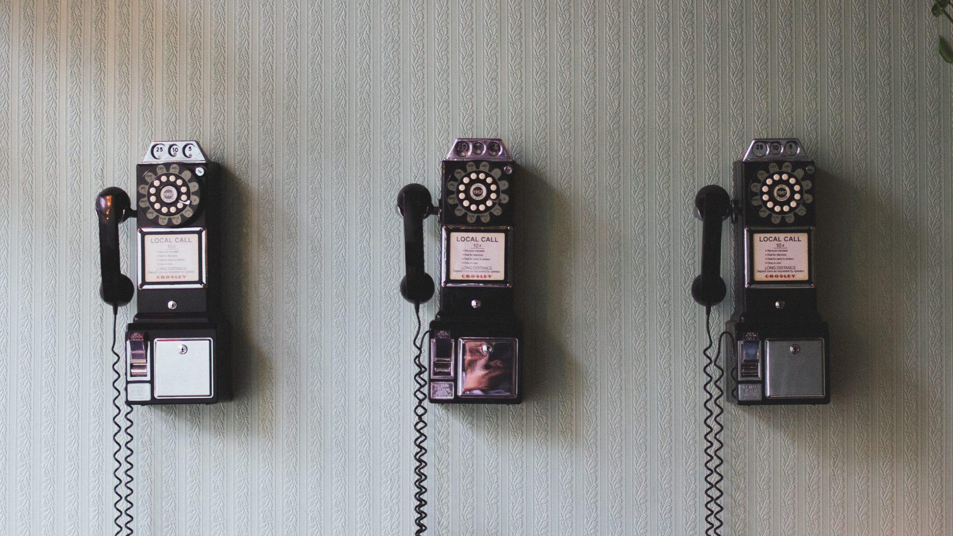 three vintage phones on a wall