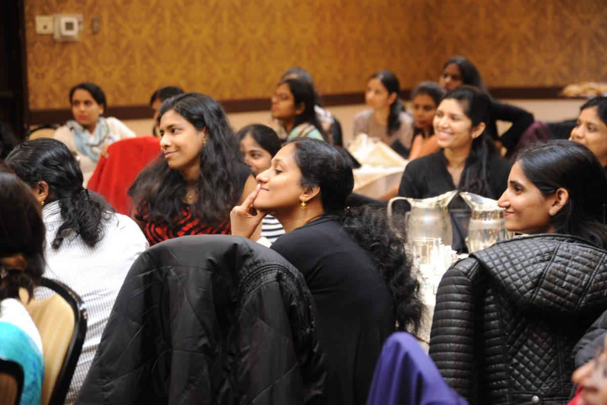 Flera kvinnor vid runda bord som lyssnar på en talare