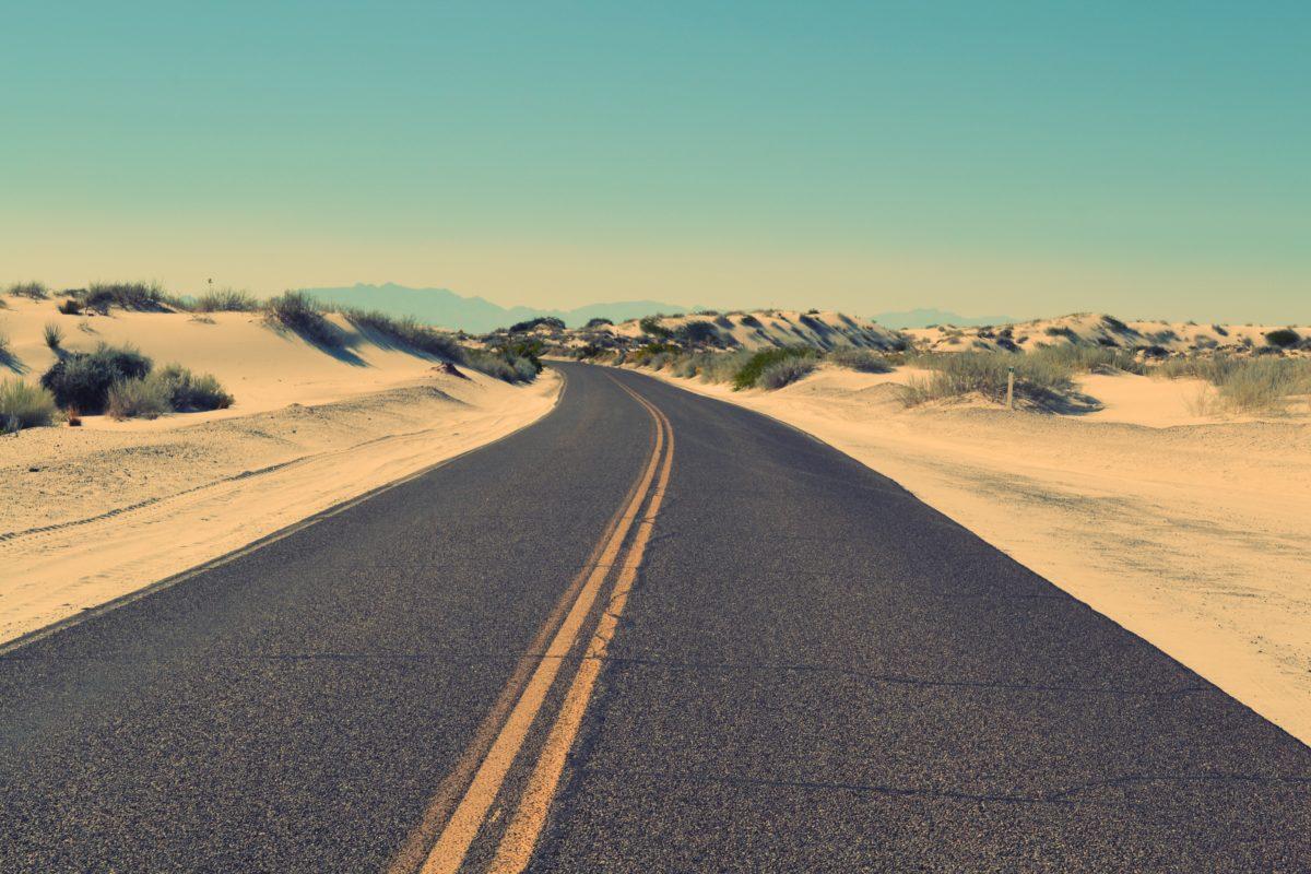 Tom landsväg omgiven av sanddynor och blå himmel
