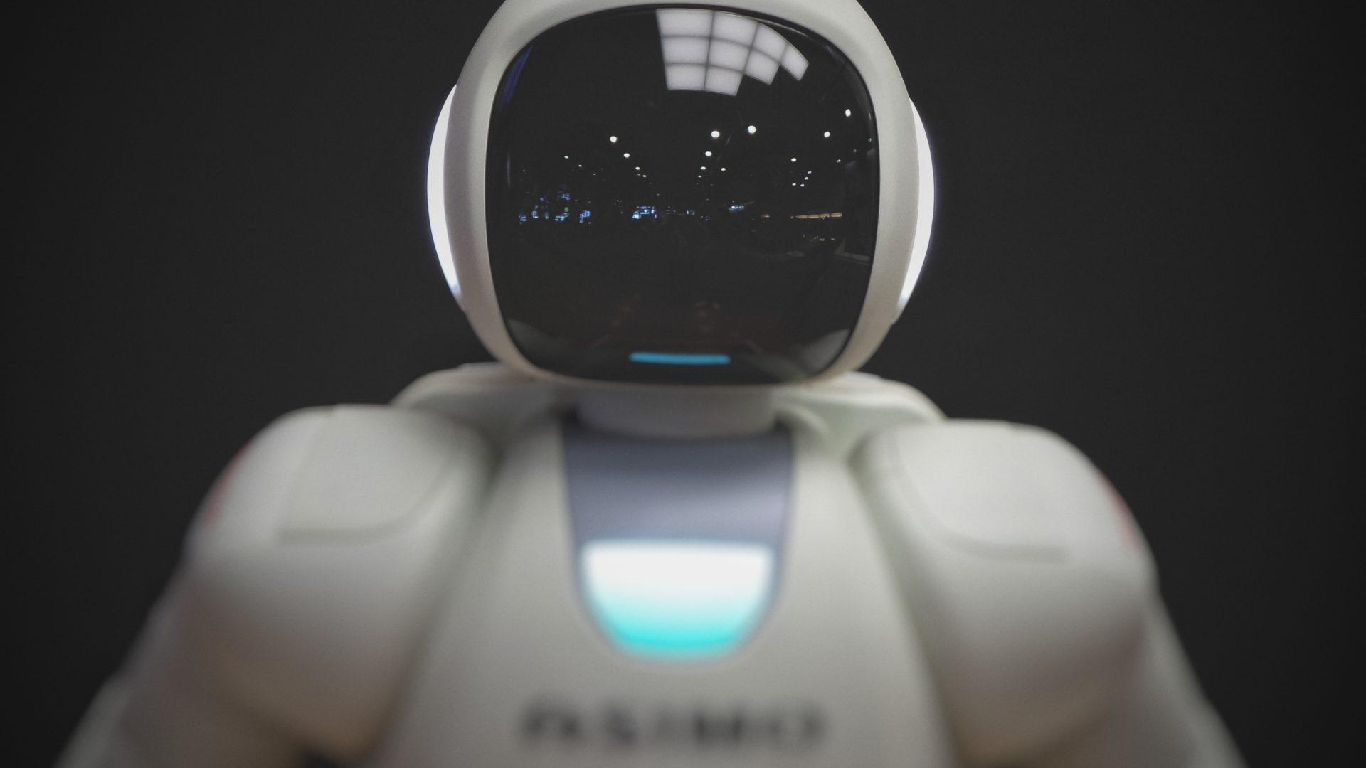 Närbild på vit robot framför svart bakgrund