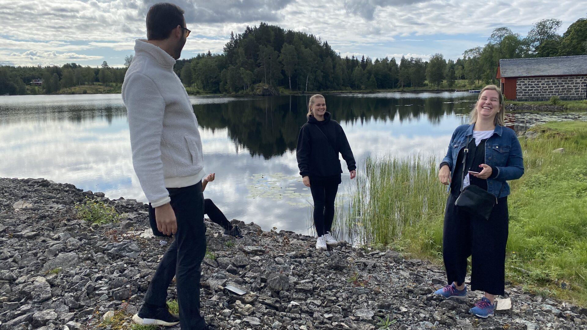 Tre personer som skrattar, i bakgrunden en stilla sjö.
